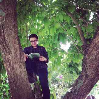 Image of Jorell Melendez Badillo reading in a tree.